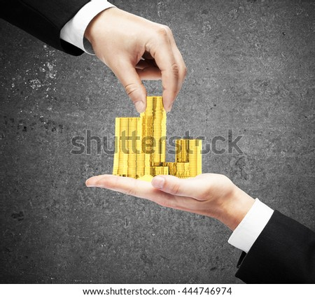 Businessmen hands holding and taking golden coins on concrete background - stock photo