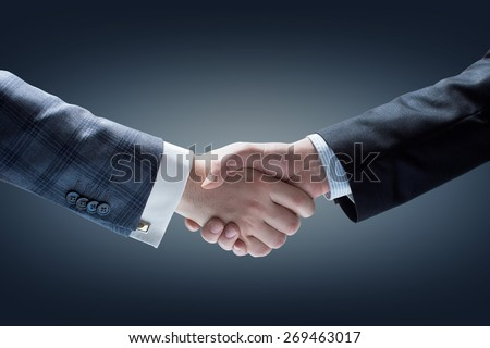 Businessmen Handshake. Hands holding on Dark Background