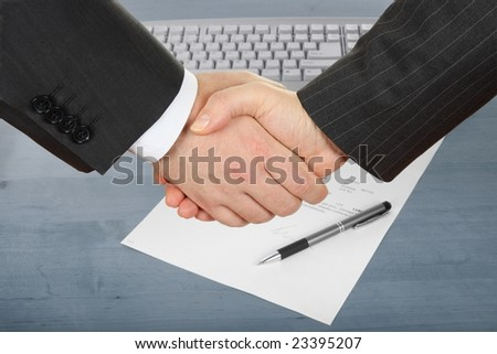 businessmen handshake over contract and pen