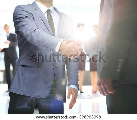 businessmen handshaking after striking deal. on a background sunrise - stock photo
