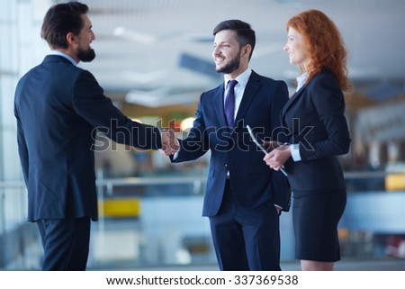 Businessmen handshaking with their colleague near by