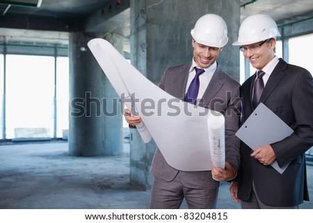 Businessmen held on site plan - stock photo