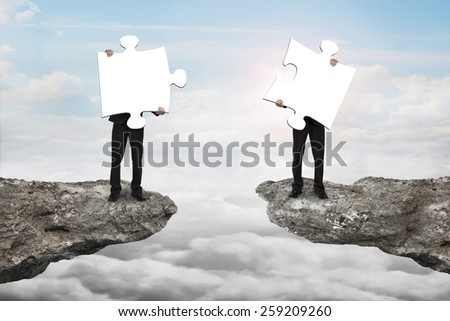 Businessmen holding two white jigsaw puzzles to connect on the cliff with cloudscape sunlight background - stock photo