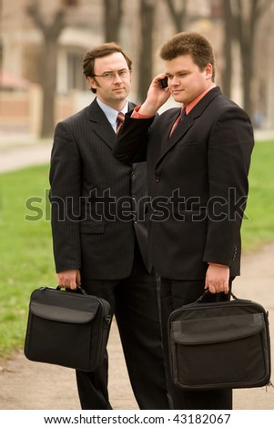 Businessmen in outdoor setting, one using mobile phone