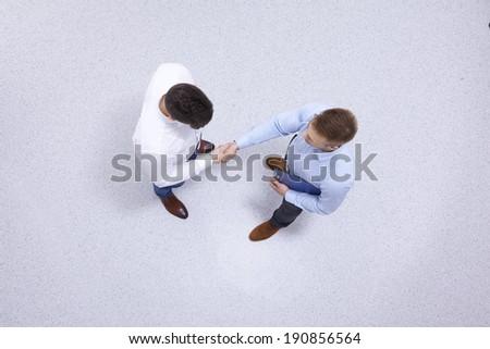 Businessmen indoors shaking hands - stock photo