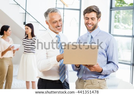 Businessmen interacting using laptop in the office - stock photo