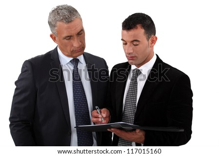 Businessmen looking at a clipboard - stock photo