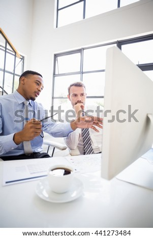 Businessmen looking at computer and interacting at a meeting in office - stock photo