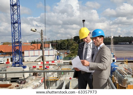 Businessmen looking at construction plan on site - stock photo
