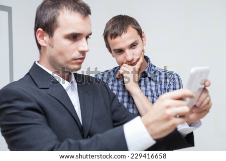 Businessmen looking at digital tablet in the office.