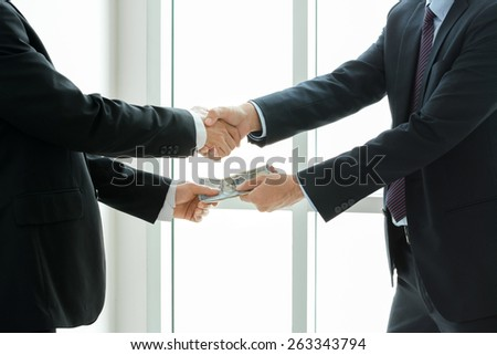 Businessmen making handshake while passing money, dealing & bribery concepts - soft focus - stock photo