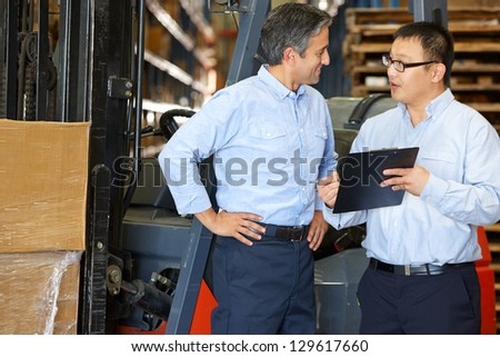 Businessmen Meeting By Fork Lift Truck In Warehouse - stock photo