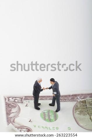 businessmen miniatures shaking hands - stock photo