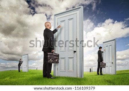 Businessmen or salesmen with briefcases knocking at several doors in a green field