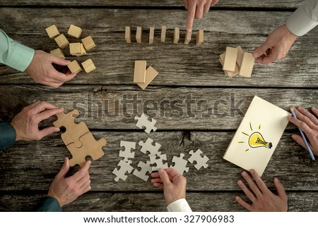 Businessmen planning business strategy while holding puzzle pieces, creating ideas with light bulb drawn on paper and rearranging wooden blocks. Conceptual of teamwork, strategy, vision or education.