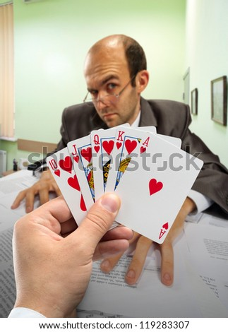 Businessmen playing poker at office