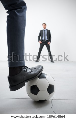 Businessmen playing soccer in an empty room, ball and foot close up with goalkeeper on background. - stock photo