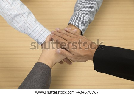 businessmen put their hand together for use as unity, cooperation and teamwork concept