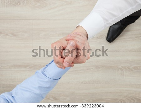 Businessmen's hands demonstrating a gesture of a strife or solidarity, view from above