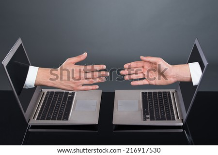 Businessmen's hands emitting from laptops representing deal over gray background - stock photo