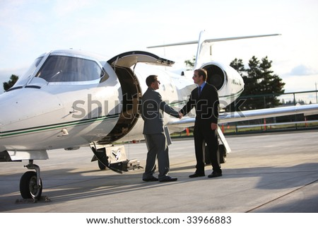 Businessmen shake hands by corporate jet - stock photo