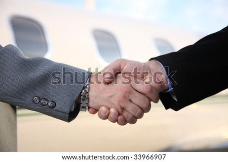 Businessmen shake hands in front of jet - stock photo