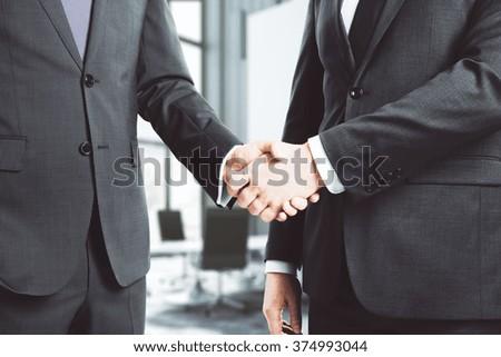 Businessmen shake hands in loft conference room - stock photo