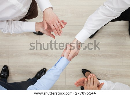 Businessmen shake hands, view from above - stock photo