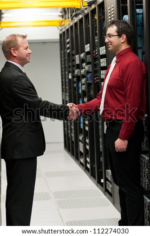 Businessmen shaking hands after making a deal - stock photo