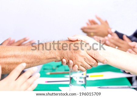 Businessmen shaking hands and congratulation by team applauding.