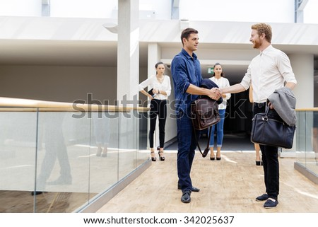 Businessmen shaking hands and greeting each other cheerfully