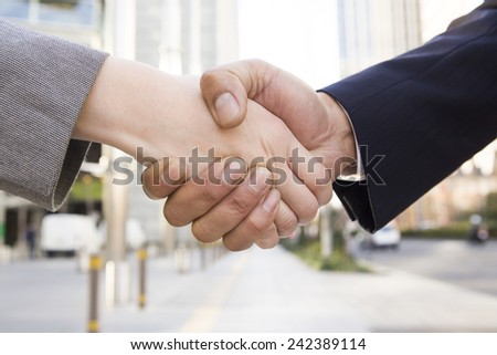 Businessmen shaking hands at office district