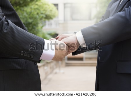 businessmen shaking hands, business concept with double exposures on handshake. Handshake is used as a commitment in business. Handshake also use as an agreement.