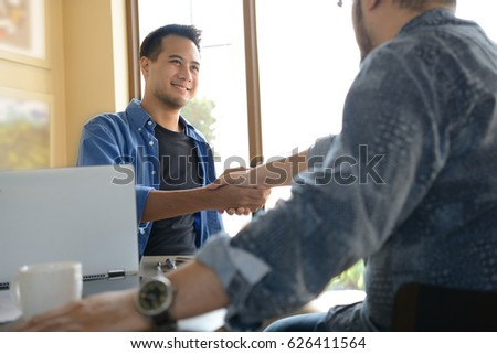 Businessmen shaking hands for business agreement in office