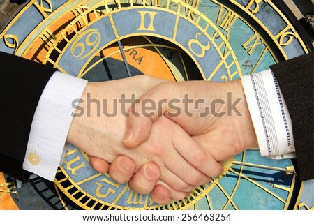 Businessmen shaking hands in front of the historical Clock - stock photo