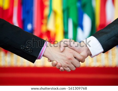 Businessmen shaking hands in front of the multi - national flag.    international business - stock photo