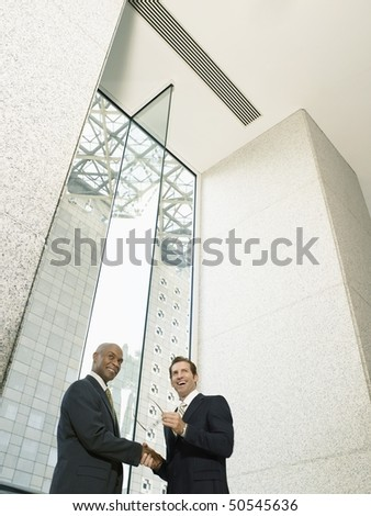 Businessmen shaking hands in office building, (low angle view)