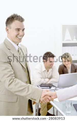 Businessmen shaking hands in office, smiling. Two busnesspersons working on the background sitting at desk.