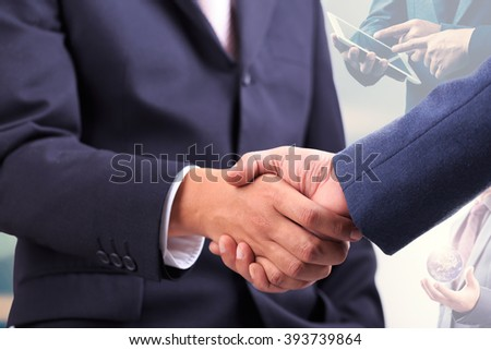 Businessmen shaking hands making an agreement with hands using tablet-pc and hand holding global in background. Elements of this image furnished by NASA. - stock photo