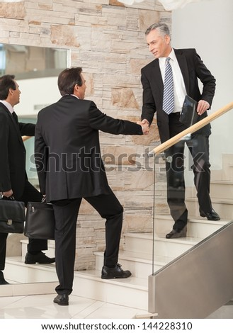 Businessmen shaking hands on steps before board meeting