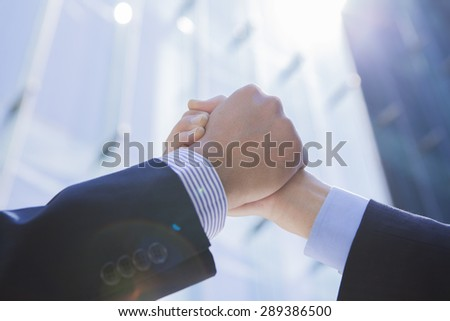 Businessmen shaking hands outside office building - stock photo