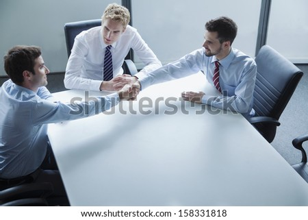 Businessmen shaking hands over the table in the office - stock photo
