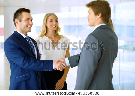 Businessmen shaking hands. Two confident businessmen shaking hands and smiling while standing at office together with people in the background