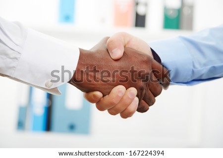 Businessmen shaking hands while in their office - stock photo