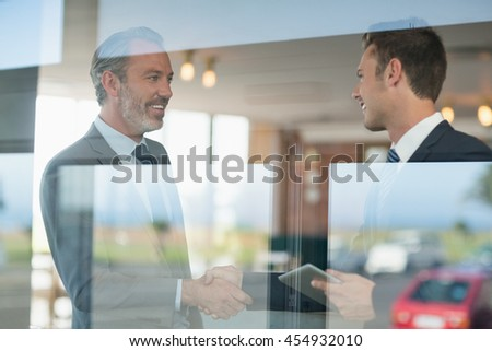 Businessmen shaking hands with each other in restaurant