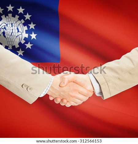 Businessmen shaking hands with flag on background - Burma