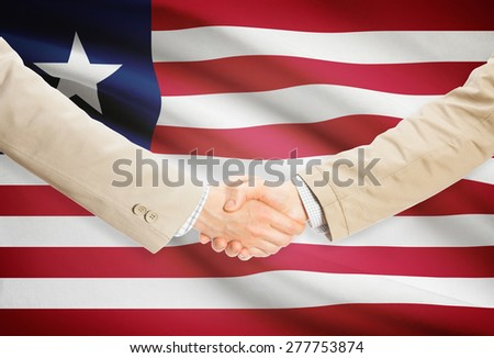 Businessmen shaking hands with flag on background - Liberia