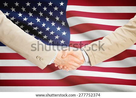 Businessmen shaking hands with flag on background - United States