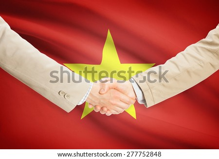 Businessmen shaking hands with flag on background - Vietnam - stock photo