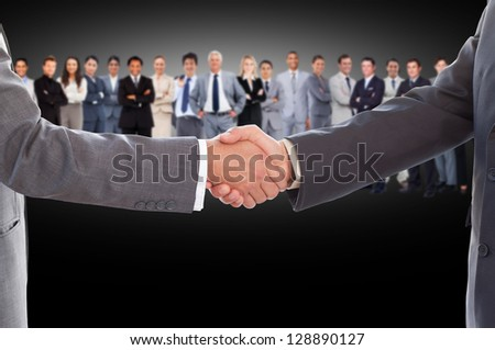Businessmen shaking hands with large business team behind them on black background